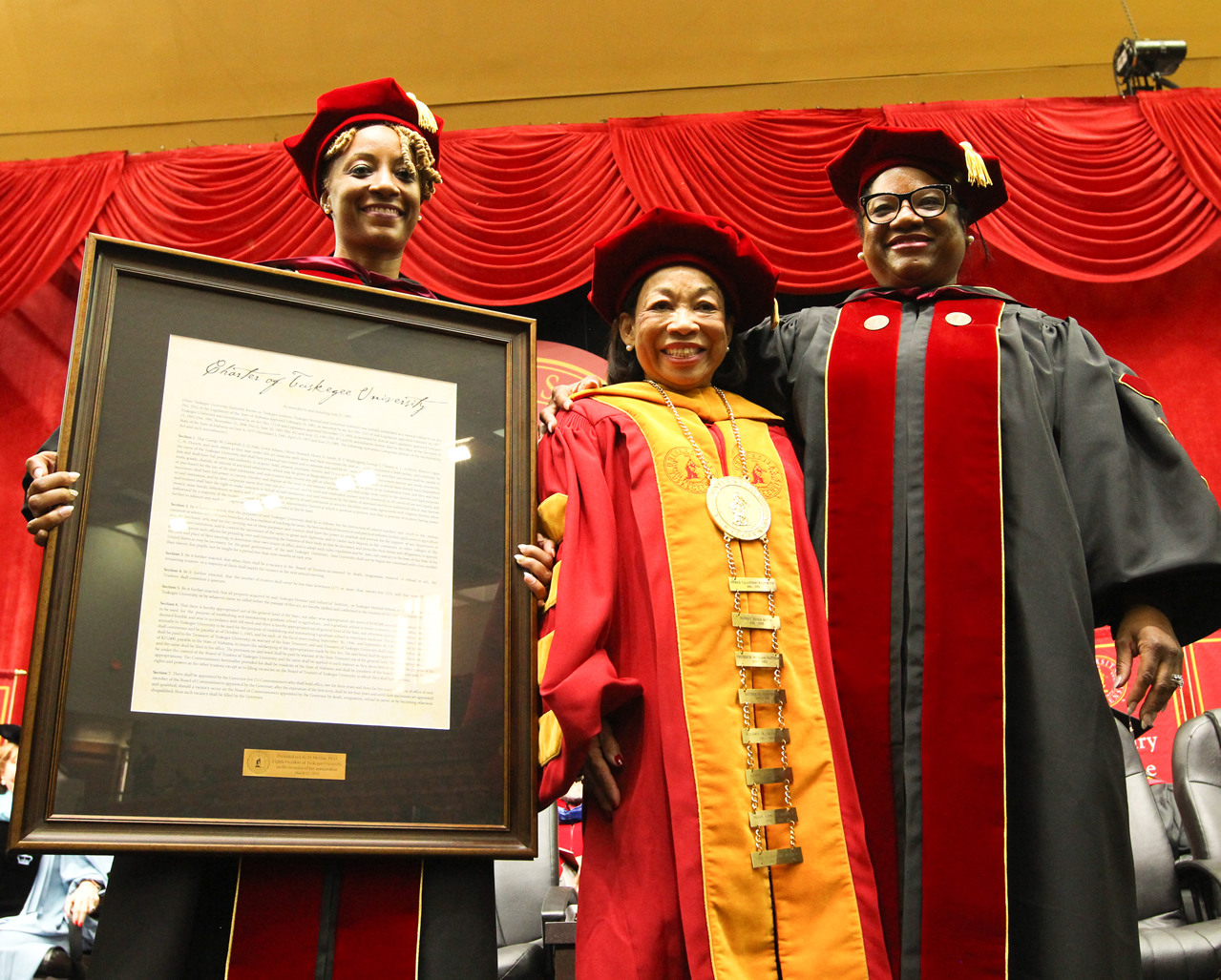 Dr. Sheena Harris and Trustee Norma Clayton present President McNair with the university charter