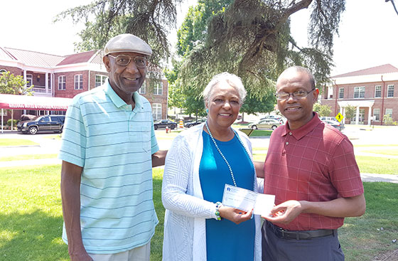 Dr. Wayne Barr receives check from Velma Blackwell's brother and sister