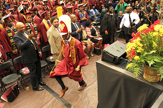 Drum Major marches in graduation gown and drum major's hat and baton