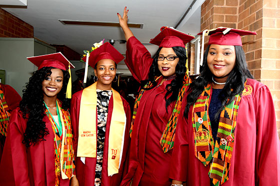 Female grads pose for picture in cap and gown