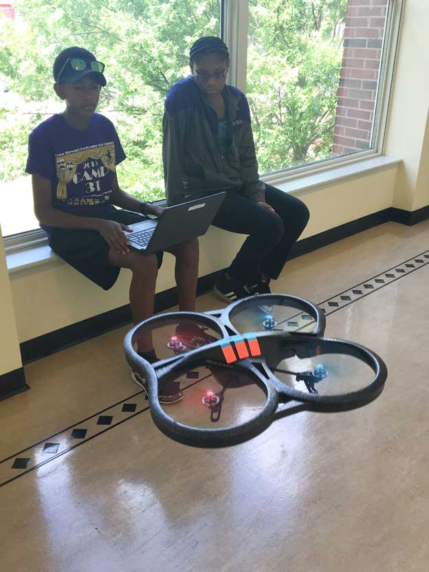 Students watch drone in hallway