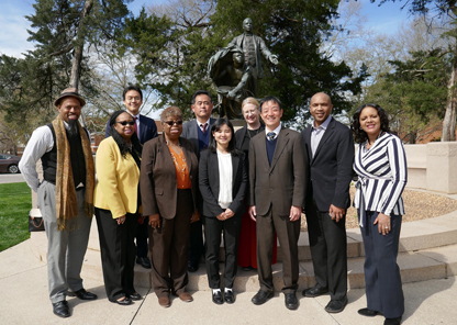 TU faculty stand with international partners in front of the Booker T. Washington statue