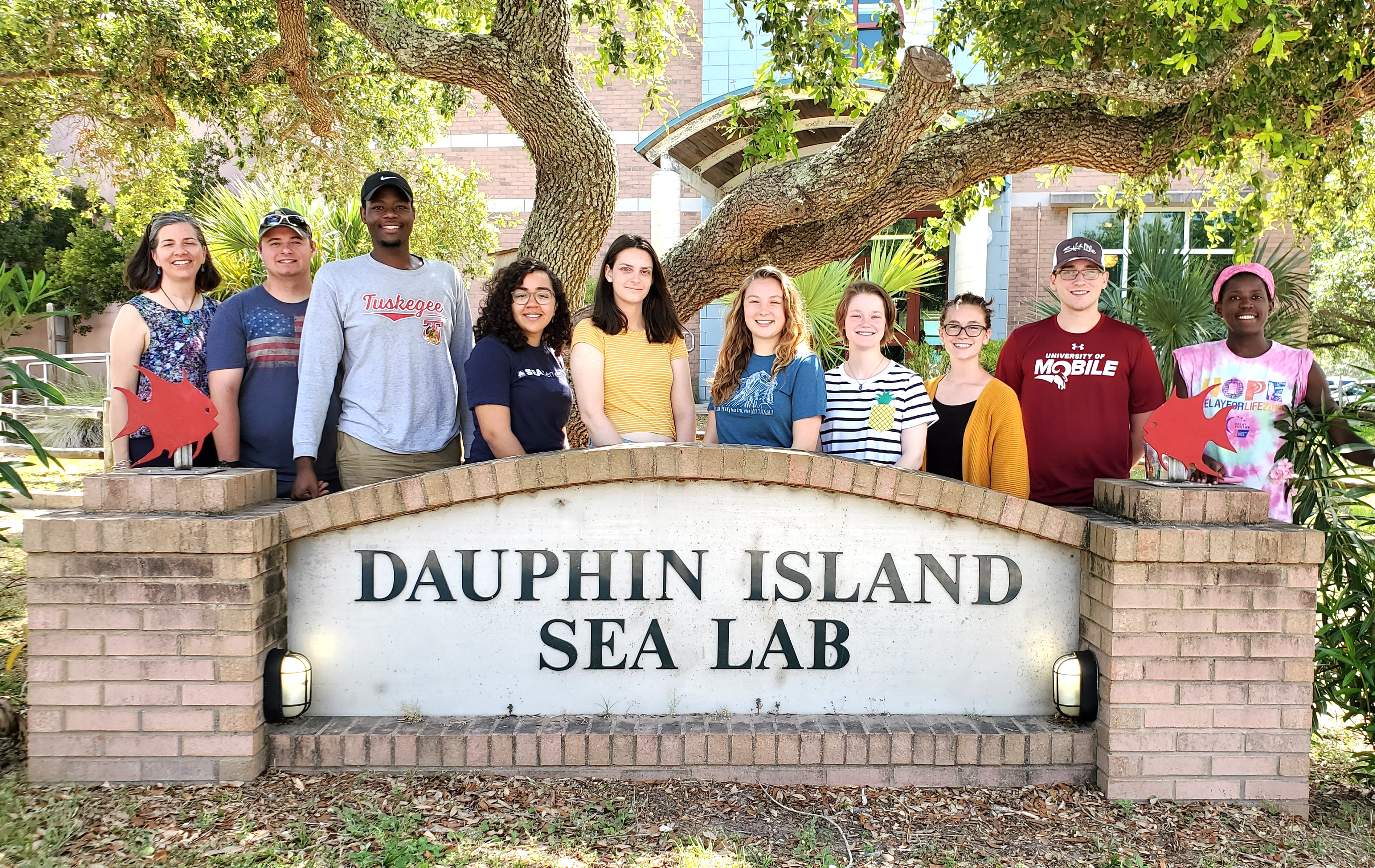 TU student Terrance Mitchell stand with Summer Research group in front of Dauphin Island Sea Lab sign