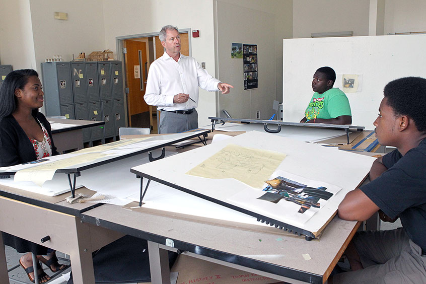 instructor talks to students in architecture classroom
