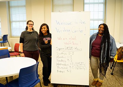 Staff member and two students stand with sign in new writing center
