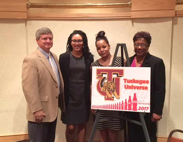 Two TU students stand with Andy Britton from Cocacola and TU Interim President Charlotte Morris