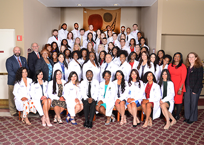 Tuskegee University Class of 2020 in white coats with special guests representing the veterinary medical associations in attendance and college administration.