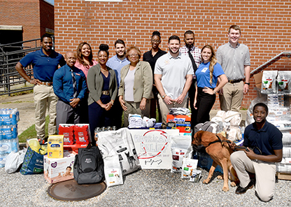 administration and student representatives stand with donated items.