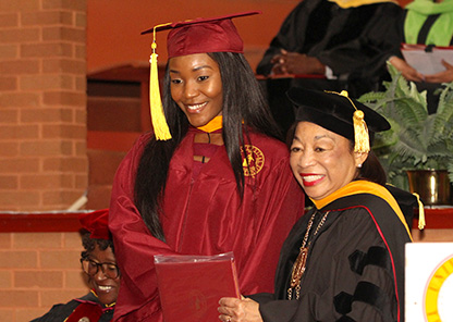 Dr. Lily McNair presents degree to a female graduate