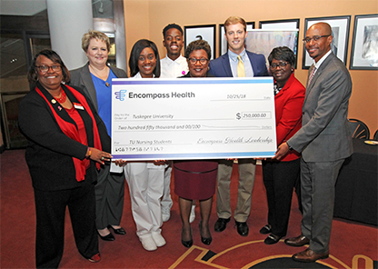 Tuskegee University officials and Encompass Health representatives pose with check.