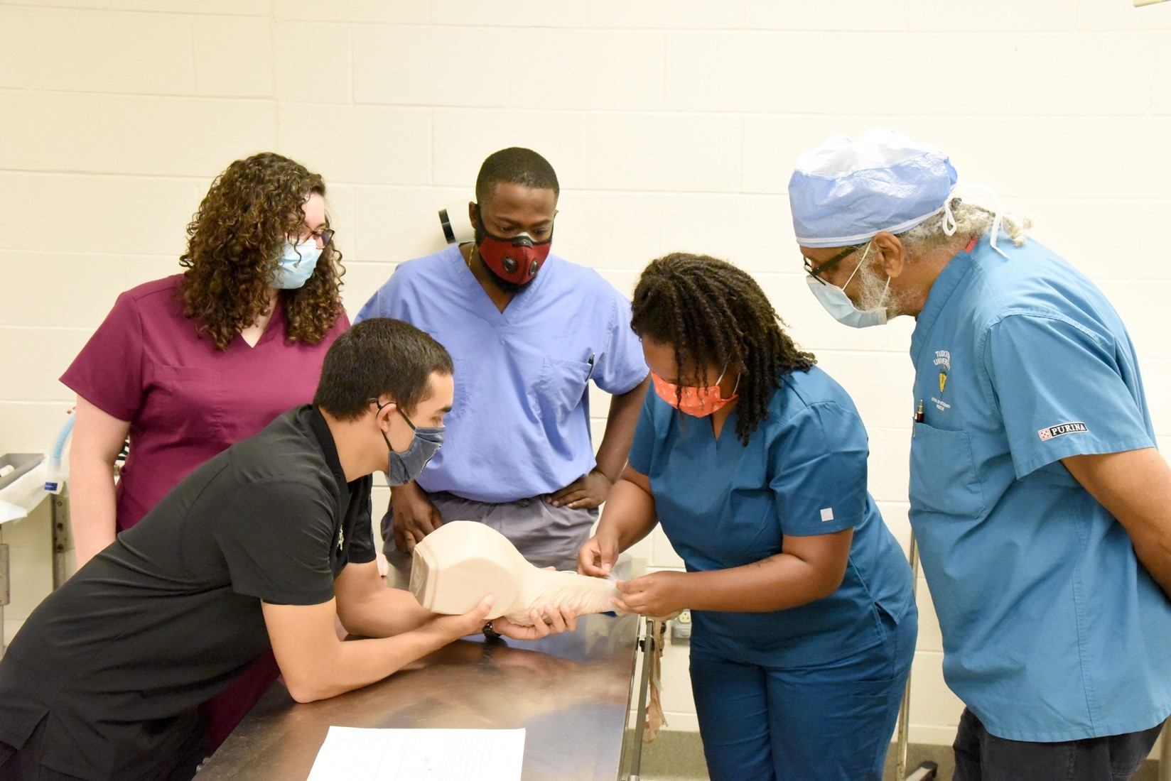 Tuskegee veterinary students in junior surgery are being instructed by clinicians Dr. Lorraine Linn and Dr. Howard King.