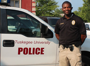 TU police officer standing next to car